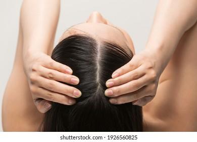 A woman is massaging the scalp.