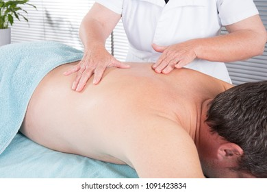 woman masseur doing massage on man body in the spa salon. Beauty treatment concept