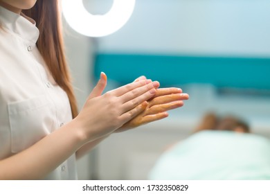 A woman masseur is rubbing her hands with honey before massage