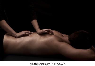 Woman masseuse giving a man a back massage
