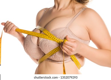 Woman measure her huge breasts with measuring tape on white background
