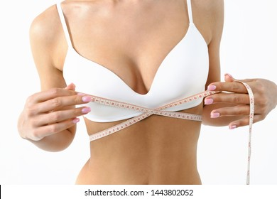 Woman with measure tape. Beauty perfect slim body: fit sporty and healthy woman posing at white background in underwear. Sport, wellness, fitness, diet, weight loss and healthcare concept