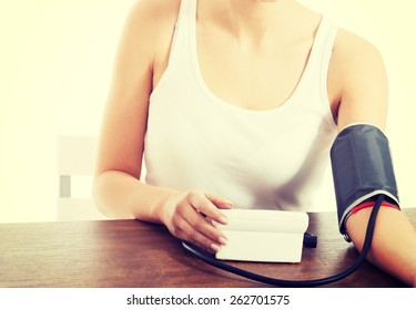 Woman measures her blood pressure.