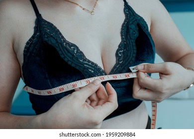 A woman measures her breast size with a tape measure while at her room. Measuring in inches.