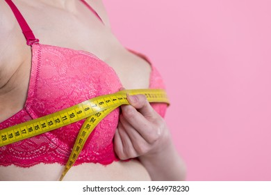 Woman measures her bust circumference. Young girl on pink background wearing pink bra. Close-up view.