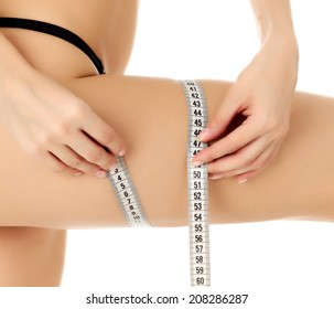 Woman measures her thigh, white background, copyspace