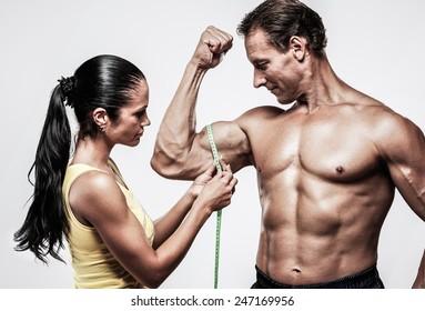 Woman measuring athletic's man biceps