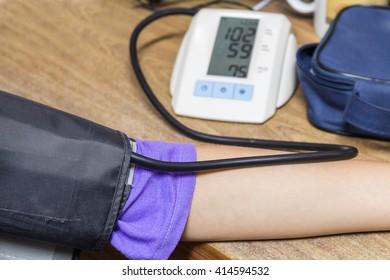 Woman Measuring Blood Pressure At Desk