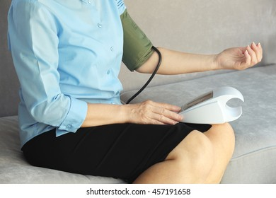 Woman measuring blood pressure herself with tonometer