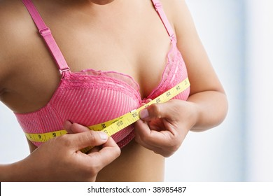 Woman measuring breast size with yellow measuring tape on room.