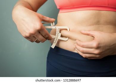Woman measuring her body skin fat with fat caliper