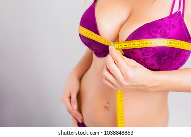 Woman measuring her breast size with measuring tape