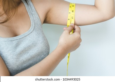 Woman measuring her excess arm fat by yellow measure tape on isolated background.