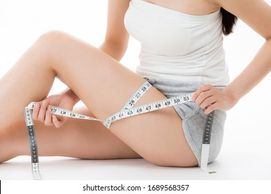 A woman measuring her thigh with a measure.