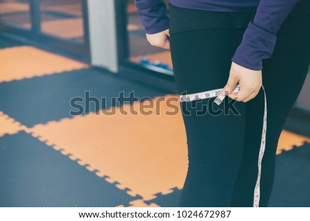 woman is measuring her thigh with measuring tape, fat woman on gym. woman's leg. She is measuring her thigh with a white metric tape measure. Beauty ,Health and weight loss concept