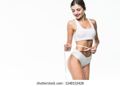 Woman is measuring her waistline against gray background in studio
