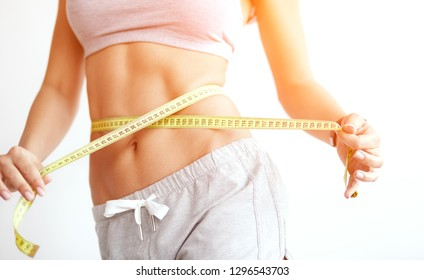 Woman measuring her waistline. Closeup of unrecognizable female with perfect slim body and torso. Healthy nutrition and weight losing concept.