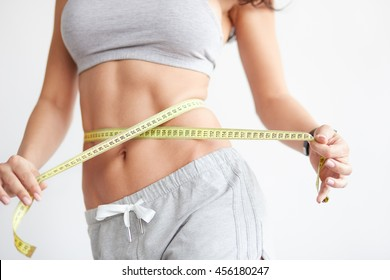 Woman measuring her waistline. Closeup of female with perfect slim body and torso. Healthy nutrition and weight losing concept.