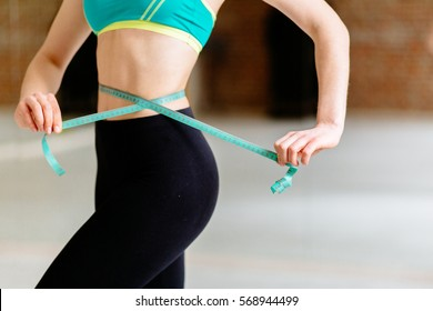 Woman measuring perfect shape of beautiful waist, healthy lifestyles concept.