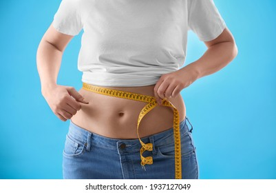 Woman with measuring tape on light blue background, closeup. Overweight problem after New Year party