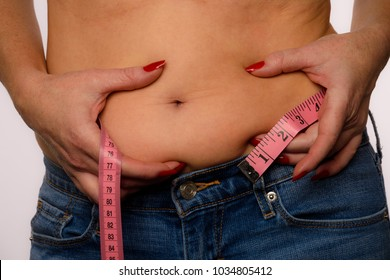 Woman With Measuring Tape Showing Belly Bulge On A White Background
