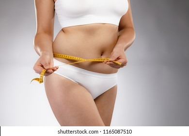 Woman measuring waist on gray background