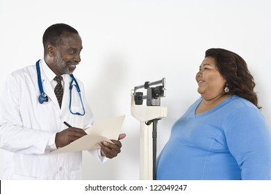 Woman measuring weight while doctor writing notes in clinic