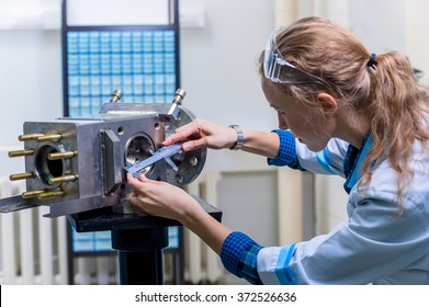 Woman mechanic with a caliper measuring device