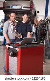 Woman mechanic going over work order on laptop with customer man