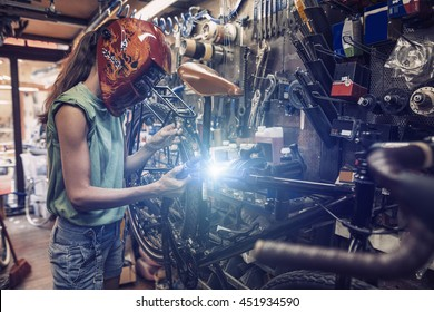 woman mechanic is repairing a bicycle using electric welding
