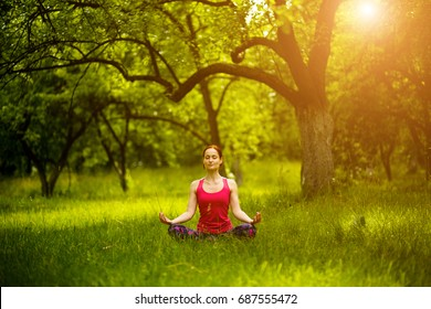 Woman mediating in yoga asana in the garden. Girl sitting in Sukhasana yoga pose with closed eyes. Toned image.