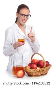 Woman in medical gown and spectacles holds a glass of juce, near there is a basket with apples and basket with apples amd a jug with juce