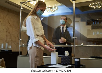 Woman in medical mask applying drops of sanitizer on her hands while a man in dark suit waiting behind the glass screen