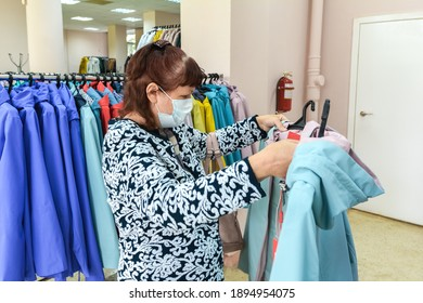 a woman in a medical mask chooses a jacket for spring in a clothing store