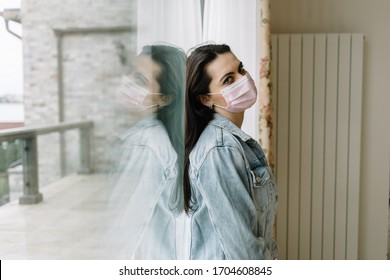 Woman in medical mask near window. Quarantine at home.