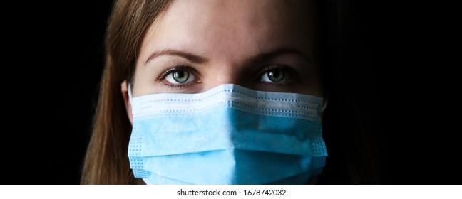 Woman in medical mask on black background. Time of quarantine. Coronavirus pandemia. Virus danger infection. Cold or flu illnesses.