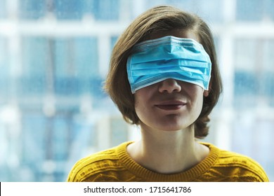 Woman in medical mask on eyes. Panic, fear, lying or disinformation during coronavirus pandemic concept.