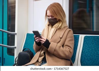 Frau in medizinischer Maske mit Telefon in ihren Händen sitzen in der U-Bahn-Auto. Coronavirus-Epidemie
