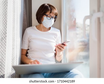 Woman in medical mask with smartphoneremote works from home. She sits on window sill with laptop on knees. Lockdown quarantine because of coronavirus COVID19. Self isolation at home.