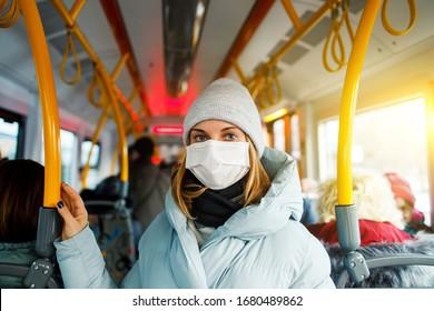 Frauen in medizinischer Maske, die nachmittags in der Buslounge neben gelben Handläufen stehen.