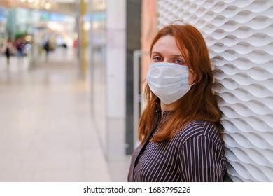 Eine Frau in einer medizinischen Maske steht während einer Epidemie des Coronavirus an einer Mauer in einem leeren Laden