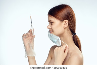 Woman in a medical mask with a syringe, injection of beauty