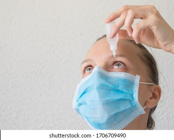 Woman in a medical mask using eye drops. Prevention of viral infections.