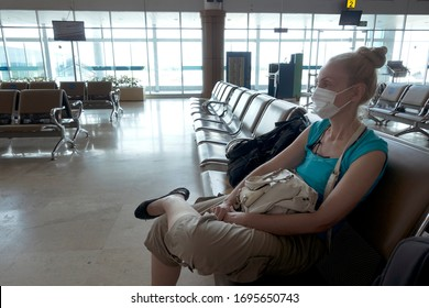 Woman in medical protective mask sits in an empty airport hall during a coronavirus pandemic.