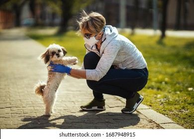 A woman in a medical protective mask is spending time with her dear cute little Shih Tzu dog on the city street path during flu virus outbreak and coronavirus epidemic.