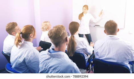 Woman medical student explaining near whiteboard in front of teacher and group of students in auditorium