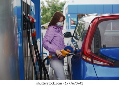 Woman in medicine mask filling car tank on a petrol station