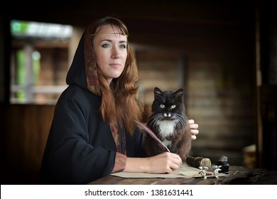 A woman in a medieval cloak sits with a pen and writes. Black cat near