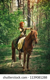 Woman in medieval dress riding horse and hunting with bow in the forest