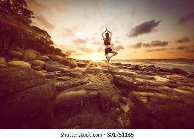 Woman meditates on rocks by the beach